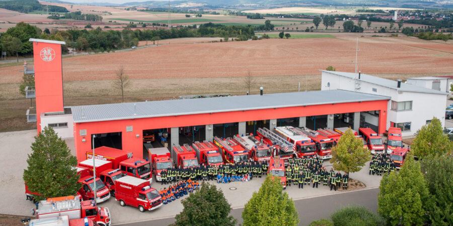 Feuerwehrautos + Feuerwehrleute vor dem Gerätehaus Gölhleim